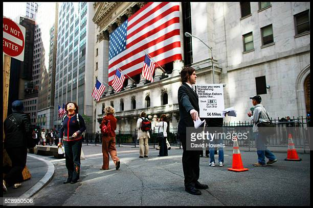 Protester Patrick Taylor hands out posters on Wall Street in front of the New York Stock Exchange