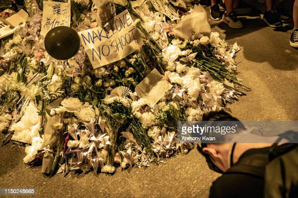 A protester pays respect during a vigil at a makeshift altar for a fellow protester who fell to his death while hanging banners on June 15 as they...