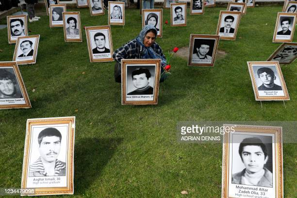Protester places flowers on a photograph of an executed man during a demonstration organised by supporters of the National Council of Resistance of...