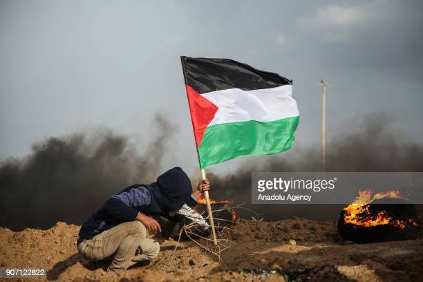A protester plants a Palestinian flag near burning tires set on fire in response to Israeli forces' intervention in a protest against US decision to...