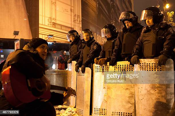 CONTENT] Protester playing guitar and singing for the riot policemen in full gear standing on the block post at main street of Kiev during Euromaidan...
