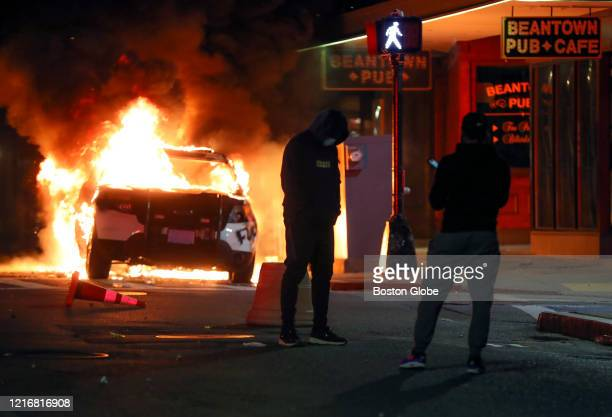 A protester poses for a photo in front of a burning Boston Police car on Tremont Street after a peaceful march from Dudley Square to the State House...