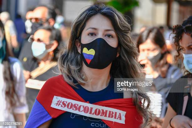 """Protester poses for a picture with a sticker saying S.O.S Colombia during a rally. The social group """"Colombians for Peace"""" gathered at the Luís de..."""