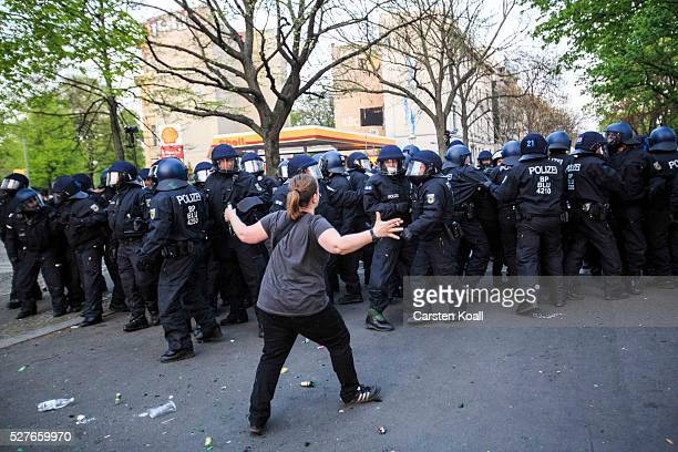 A protester poses in front of German riot policemen during clashes after a march on May Day on May 2016 in Berlin Germany Tens of thousands of people...
