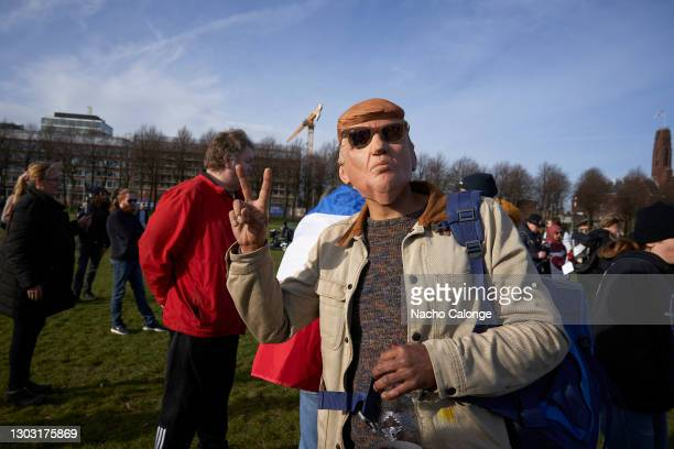 """Protester poses with a mask representing Donald Trump at the demonstration held on February 20, 2021 in The Hague, Netherlands. Organised by the """"Wij..."""