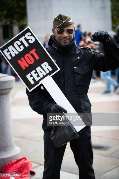 Protester posing with a placard saying, facts not fear, during the demonstration. Unite for Freedom demonstrators gather at Trafalgar Square to...
