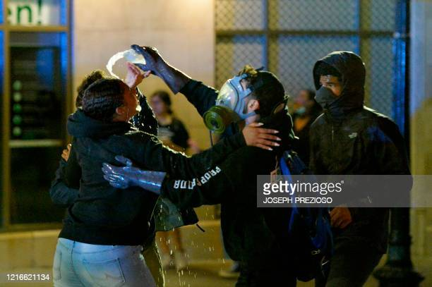A protester pours milk into the eyes of another who was sprayed with pepper spray during clashes with police after a demonstration over the death of...