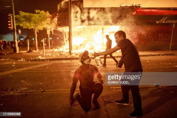 A protester pours vodka into the mouth of another in front of a liquor store in flames on May 28 2020 in Minneapolis Minnesota during a protest over...