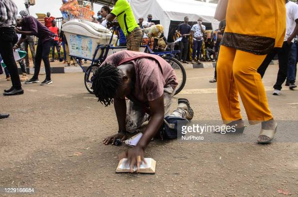 Protester prays on a Holly Bible as Christian protesters gather for Sunday services in Lagos on October 19, 2020. As Christians hold Sunday Church...