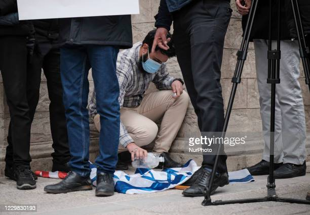 Protester prepares an Israeli flag to set on fire while attending a protest gathering against the assassination of the Iranian Top nuclear scientist...