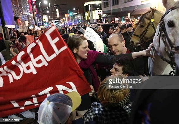 A protester pushes a police horse outside a rally for Republican presidential candidate Donald Trump at the Arvest Bank Theater in Kansas City Mo on...