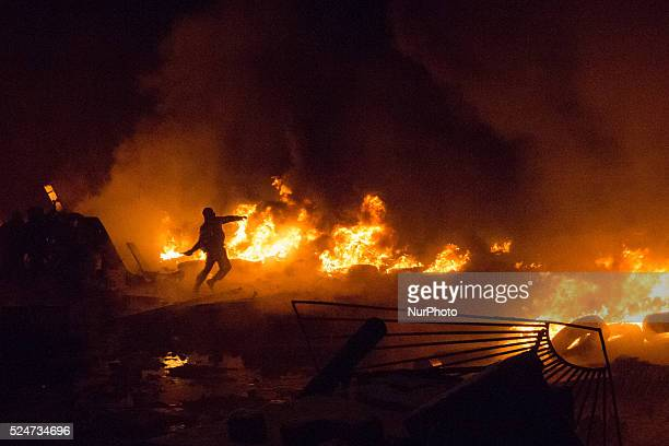 A protester pushes a tire into a fire during an antigovernment protest in downtown Kiev