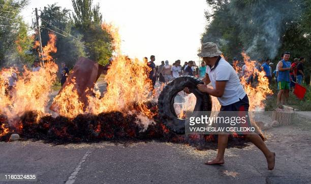A protester puts a tyre on a burning barricade during clashes between supporters of Kyrgyzstan's former president and law enforcement in the village...