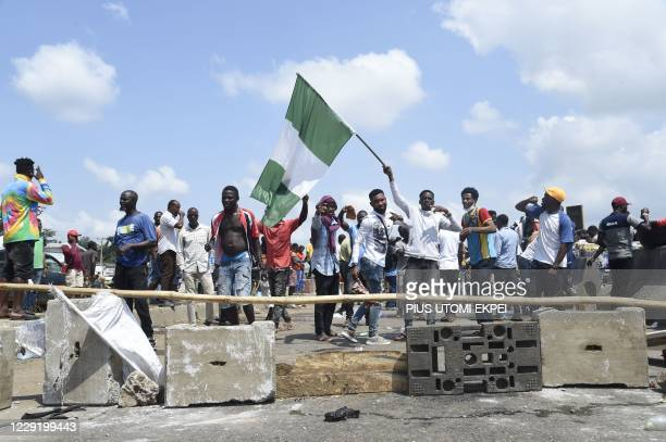 Protester raise the Nigerian national flag at a barricade mounted by potesters on the Lagos-Ibadan expressway to protest against police brutality and...