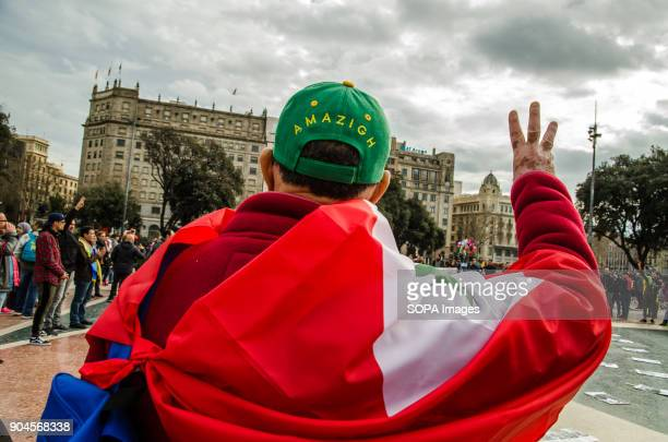A protester raised arm with the flag of the Rif on his back and a sports Cap with the text 'Amazigh writting on it Third March in Barcelona by the...