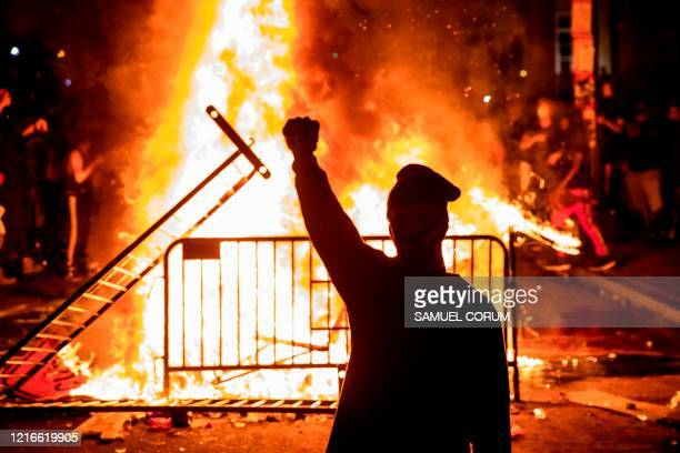 TOPSHOT A protester raises a fist near a fire during a demonstration outside the White House over the death of George Floyd at the hands of...