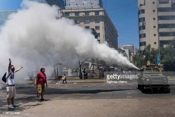 Protester raises his arms while a police vehicle throws gases during a national strike and general demonstration called by different workers unions...
