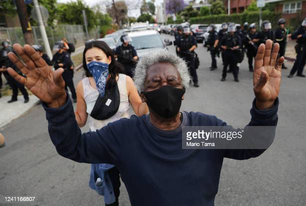 A protester raises his hands in front of police in the Hollywood area during a peaceful demonstration over George Floyd's death on June 1 2020 in Los...