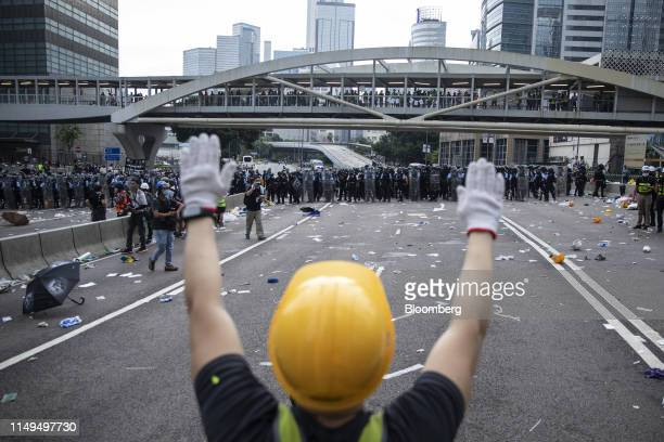 A protester raises his hands in front of riot police outside the Legislative Council building during a protest against a proposed extradition law in...