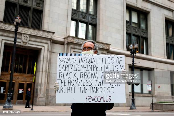 Protester Ramon Muniz holds a sign outside City Hall during a rally asking jails to release prisoners and detainees due to coronavirus in Chicago...
