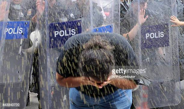 A protester reacts as he and others are sprayed by police while demonstrating against the construction of a new US Embassy Building in front of the...