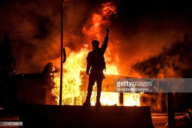 TOPSHOT A protester reacts standing in front of a burning building set on fire during a demonstration in Minneapolis Minnesota on May 29 over the...