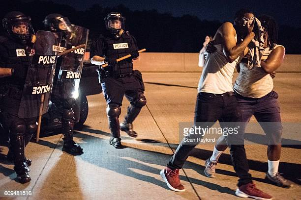 A protester reacts to a sprayed deterrent while blocking traffic on the I85 during protests in the early hours of September 21 2016 in Charlotte...