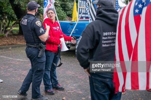 Protester reacts while speaking to a Salem police officer in front of Gov. Kate Brown's residence, Mahonia Hall, on November 21, 2020 in Salem,...