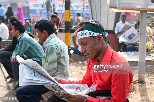 protester leyendo el periódico en square - bangladesh fotografías e imágenes de stock