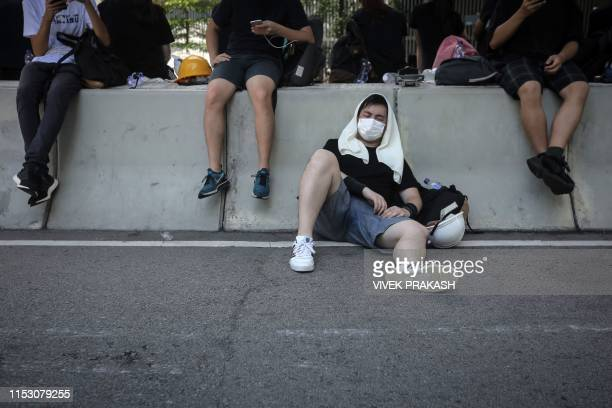 TOPSHOT A protester rests against a road divider outside the Legislative Council in Hong Kong after a flag raising ceremony to mark the 22nd...