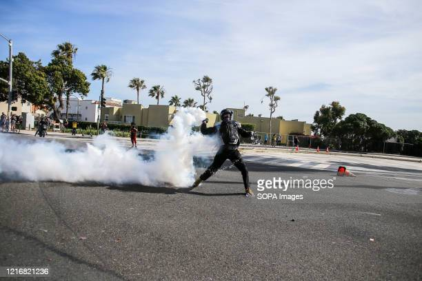 A protester return throws tear gas towards the police who fired it during a protest against the killing of George Floyd Protesters took to the...
