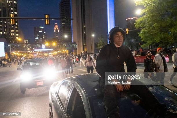 Protester rides atop a car as protesters march up North High Street following a mass 'die-in' at the Ohio Statehouse on June 1, 2020 in Columbus,...