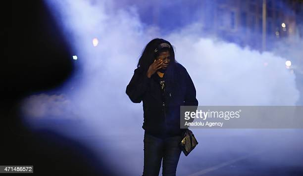 Protester rubs her eyes to avoid pepper spray fired by riot police during a curfew in Baltimore, Maryland, USA on 28 April 2015. Tensions eased on 28...