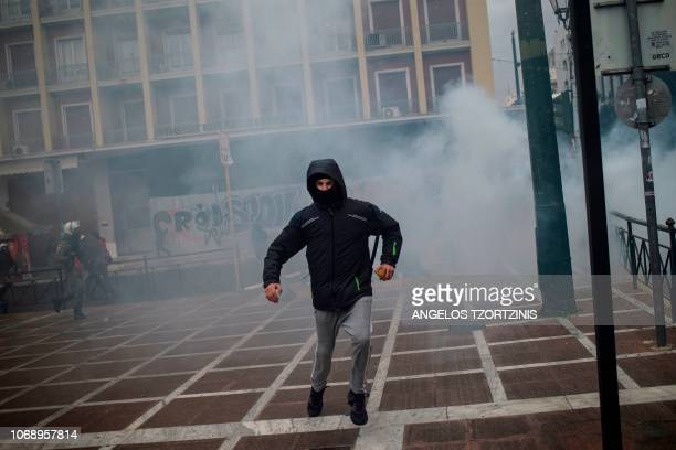 A protester runs away from tear gas during a demonstration in Athens on December 6 2018 to commemorate the 10th anniversary of fatal shooting of a...