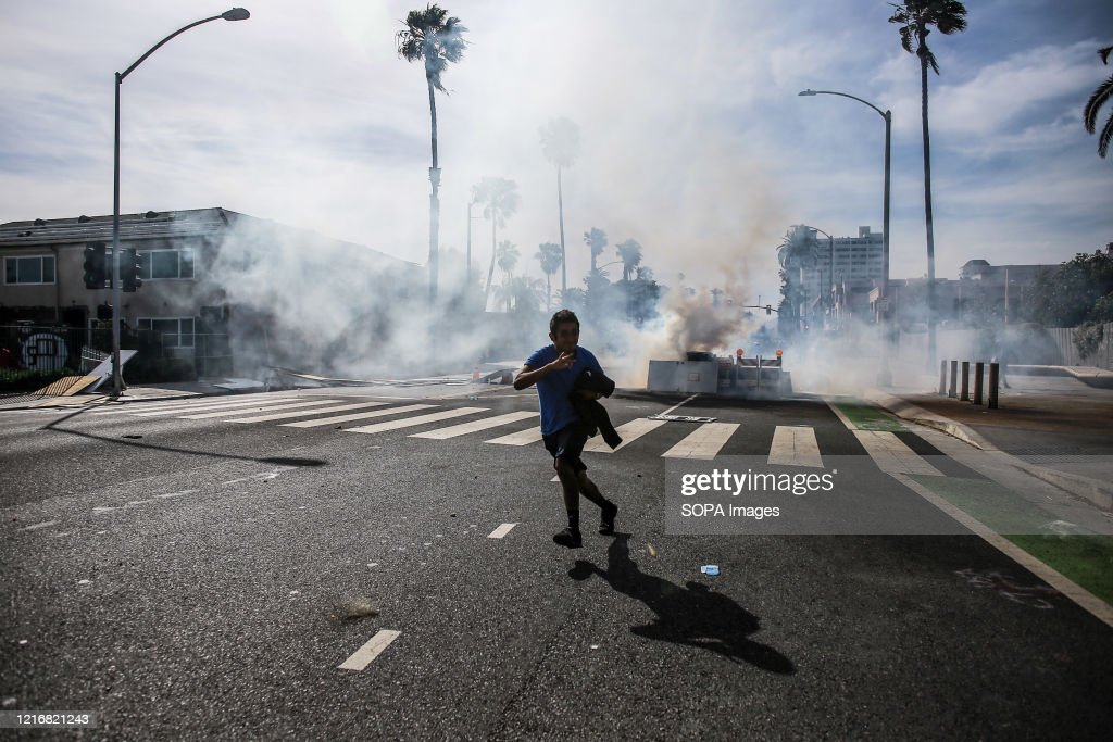 A protester runs from tear gas launched from police near the... : News Photo
