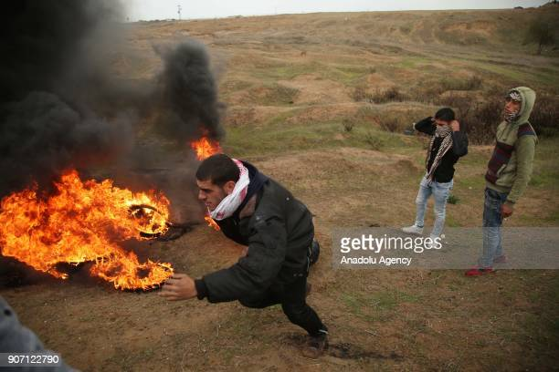 A protester runs near burning tires set on fire in response to Israeli forces' intervention in a protest against US decision to recognize Jerusalem...