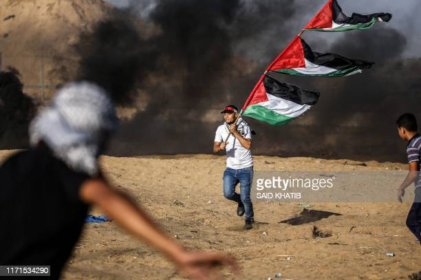 Protester runs with a pole carrying several Palestinian flag away from smoke during clashes with Israeli forces following a demonstration along the...