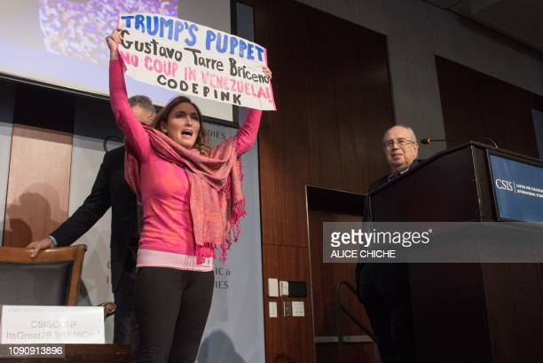A protester rushes the stage as Gustavo Tarre speaks at the Center for Strategic and International Studies in Washington DC on January 29 2019 Tarre...