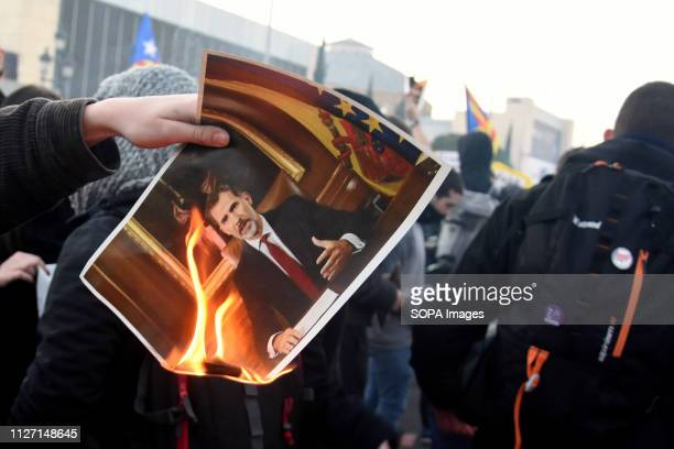 A protester seen burning a placard with a photo of the King of Spain Felipe VI during the protest Hundreds of people demonstrate against the presence...