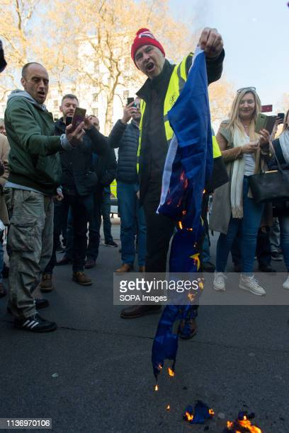 A protester seen burning the EU flag during the demonstration Protesters gathered at Parliament Square and marched to different places including...