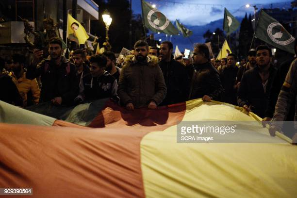 Protester seen carrying a larger kurdish flag during the demonstration Kurds march to the Turkish embassy protesting for the bombing of Kurdish...