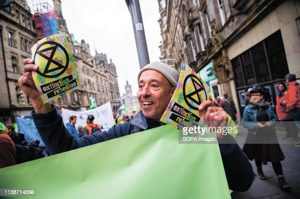 A protester seen holding a banner during the demonstration Extinction Rebellion held a lockdown of Edinburgh's North Bridge as part of an...