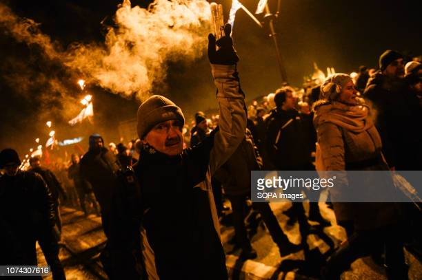 A protester seen holding a burning flare during the protest against the new labour law approved by the right wing conservative government lead by...