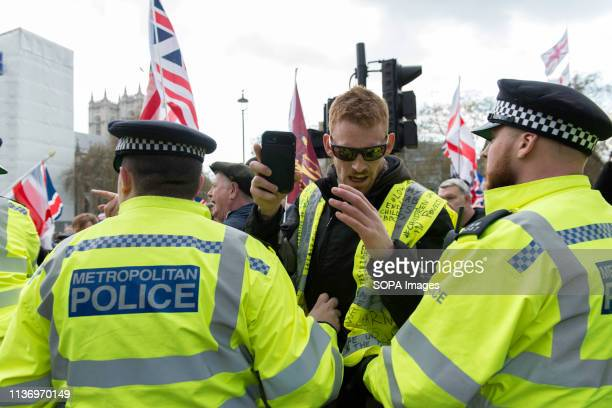A protester seen holding a mobile phone in front of the police officers during the demonstration Protesters gathered at Parliament Square and marched...