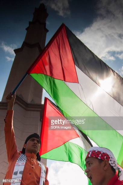 A protester seen holding a Palestine flag during a demonstration Hundred of Malaysian people had gathered at Putrajaya Mosque to demonstrate against...