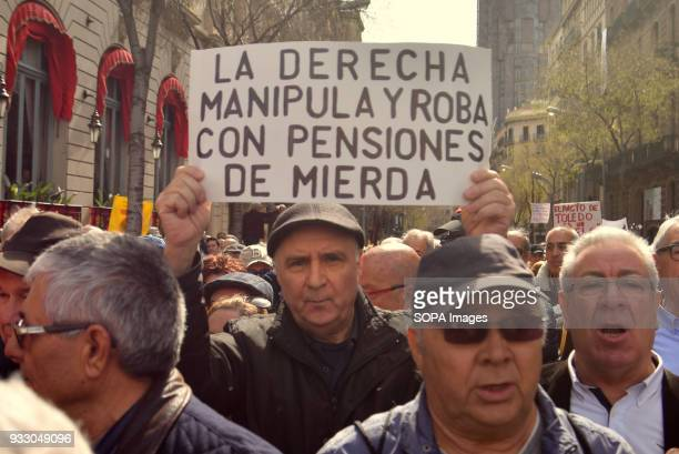 A protester seen holding a placard during the demonstration Ten of thousands of pensioners took to the street of Barcelona during a protest called by...