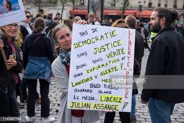 A protester seen holding a placard raising awareness of Julian Assange during the May Day protests in Paris May Day is a public holiday celebrated...