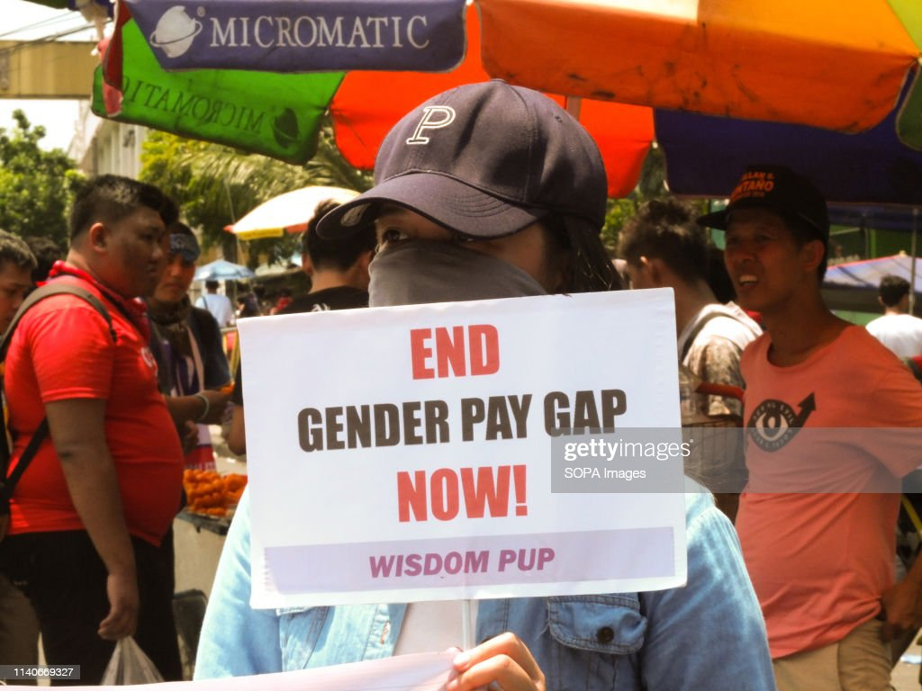 A protester seen holding a placard that says end gender pay... : News Photo