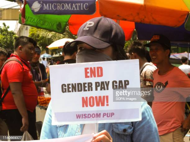 Protester seen holding a placard that says end gender pay gap now during the Labour Day Protest in Manila. Workers marched from Welcome Rotonda in...