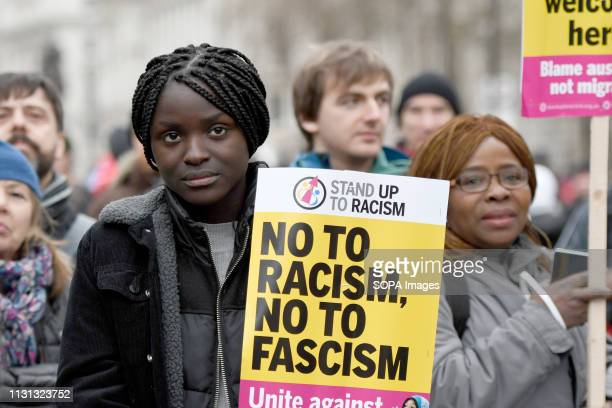 A protester seen holding a placard that says no to racism no to fascism during an anti racist rally Antiracists gathered at Park Lane and marched...